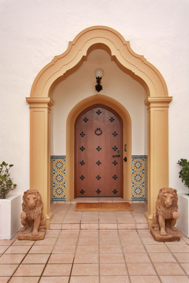 Mediterranean exterior white stucco exterior walls light brown tiles floors wood front door with black wrought iron accents a pair of lion statues