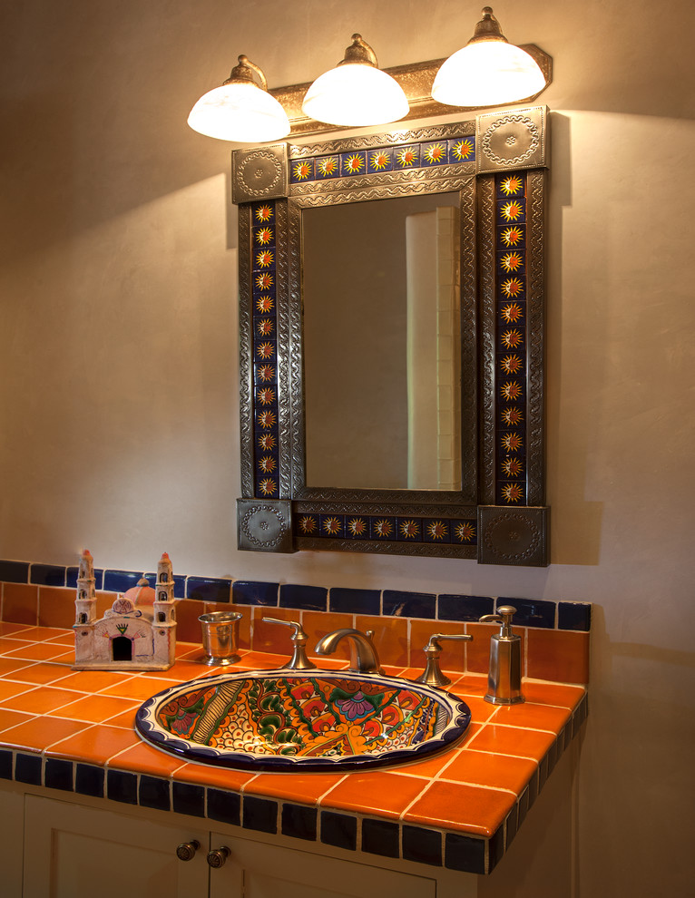 Southwest bathroom vanity idea orange tiles countertop undermount sink with motifs mirror with artistic metal frame three units of vanity lamps on top flat paneled cabinets