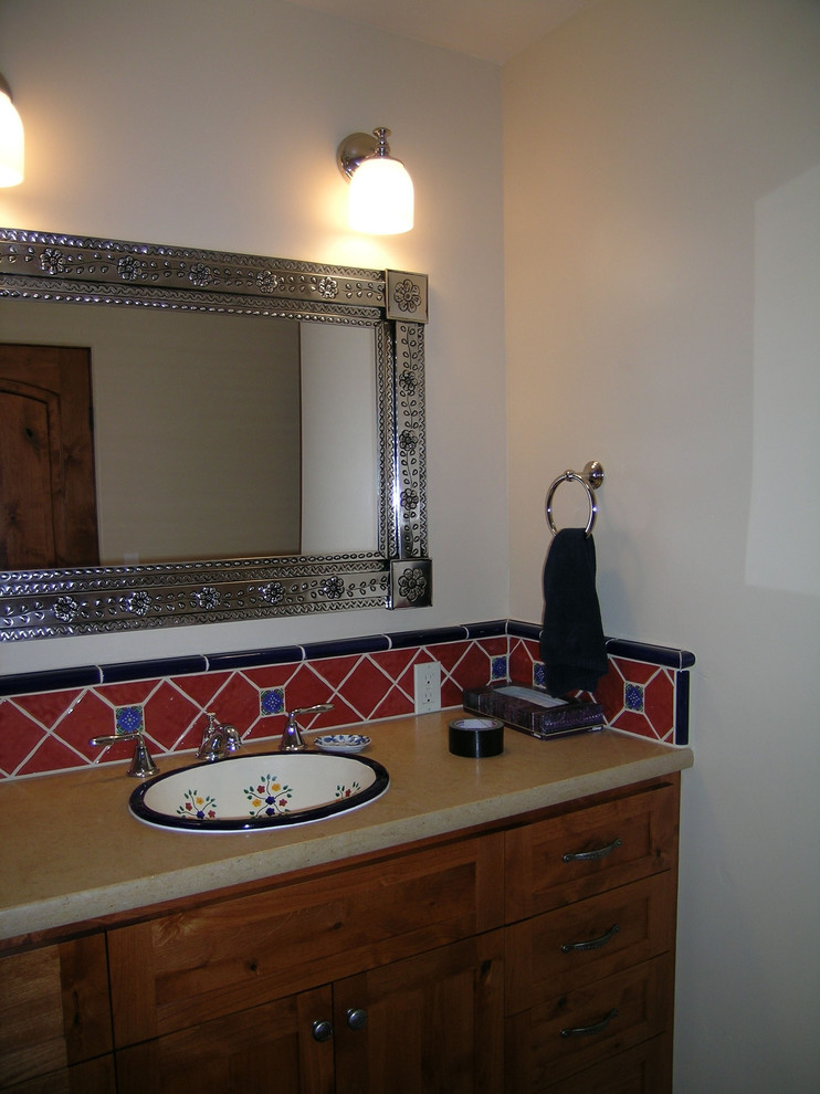 Southwest style bathroom vanity undermount sink with multicolored motifs red tiles backsplash with blue accents fancy mirror with iron brass frame wood like laminate countertop wood cabinets