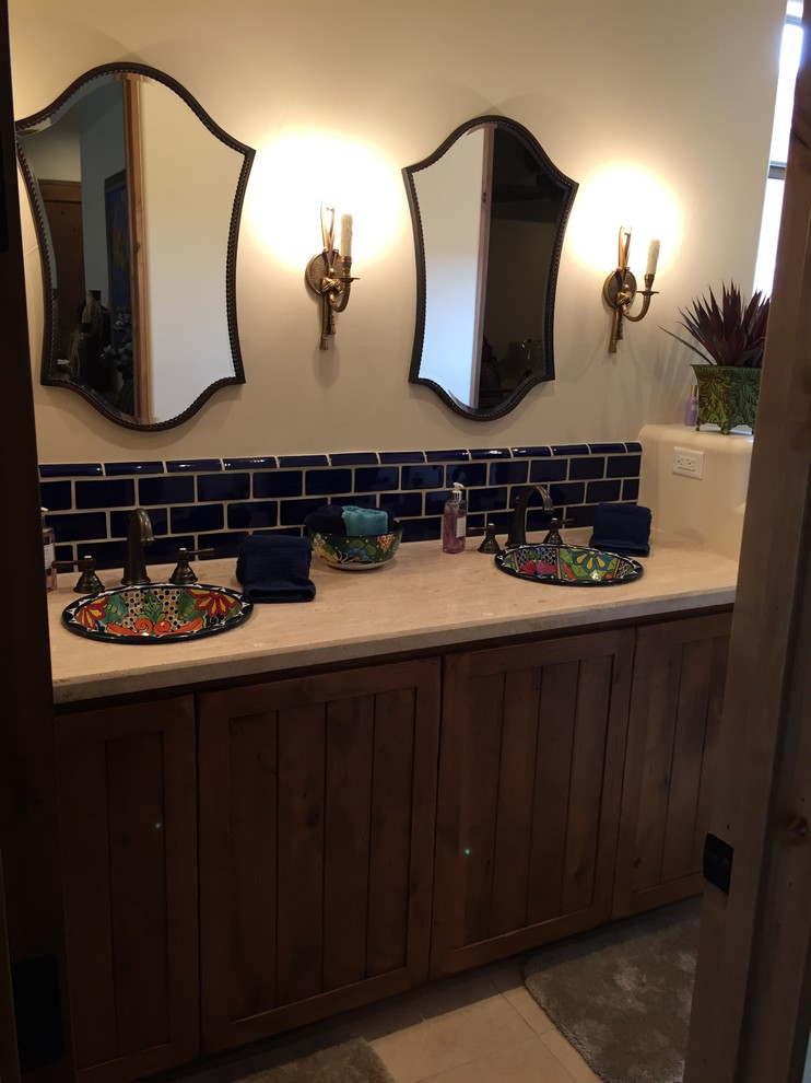 Southwestern bathroom idea plain countertop undermount sinks with multicolored motifs dark blue tiles backsplash dark wood cabinets
