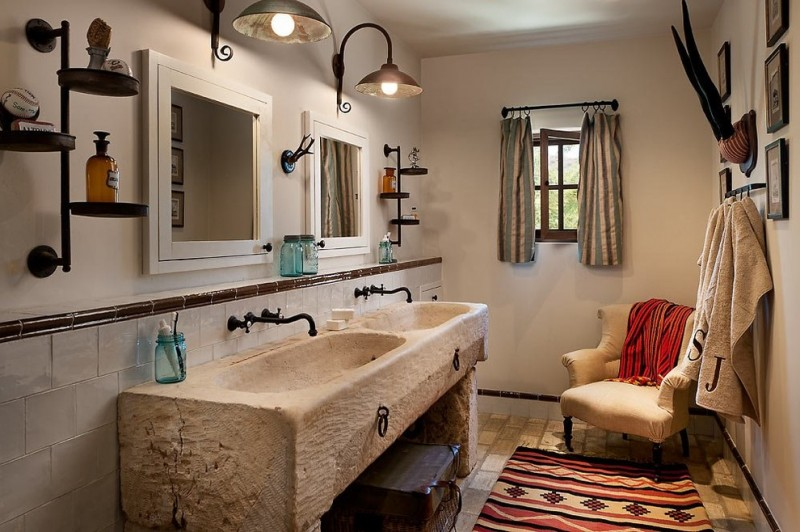 Southwestern style bathroom vanity with integrated sinks white framed mirrors dark brass iron fixtures traditional wall lamps wall mounted tree for shelving