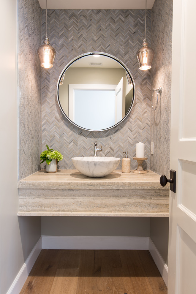 beach style vanity light hardwood counter marble vessel bowl sink beige walls medium toned wood floors rounded mirror with chrome frame a couple of pendant lamps