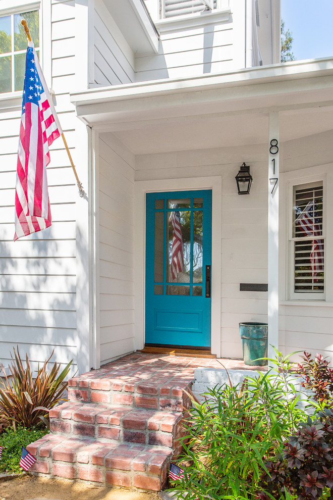 bright blue finishing colonial front door with clear glass window accent white exterior walls white siding exterior walls red bricks flooring idea