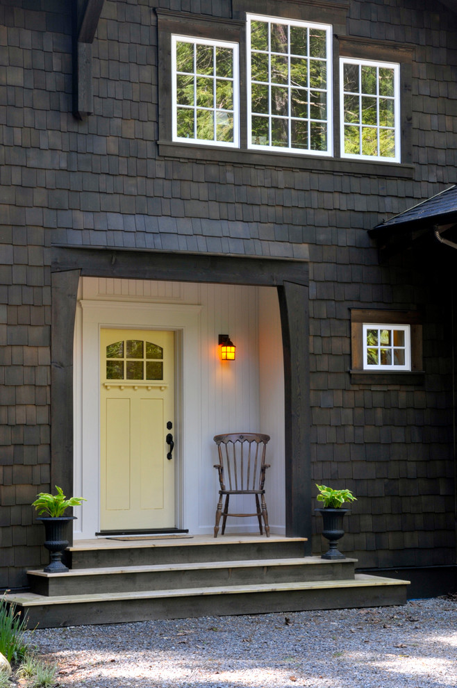 cananga yellow finishing colonial front door with transom addition and black wrought iron handler small sized exterior wall lamp simple wood chair white siding exterior wall black wood shingles exteri