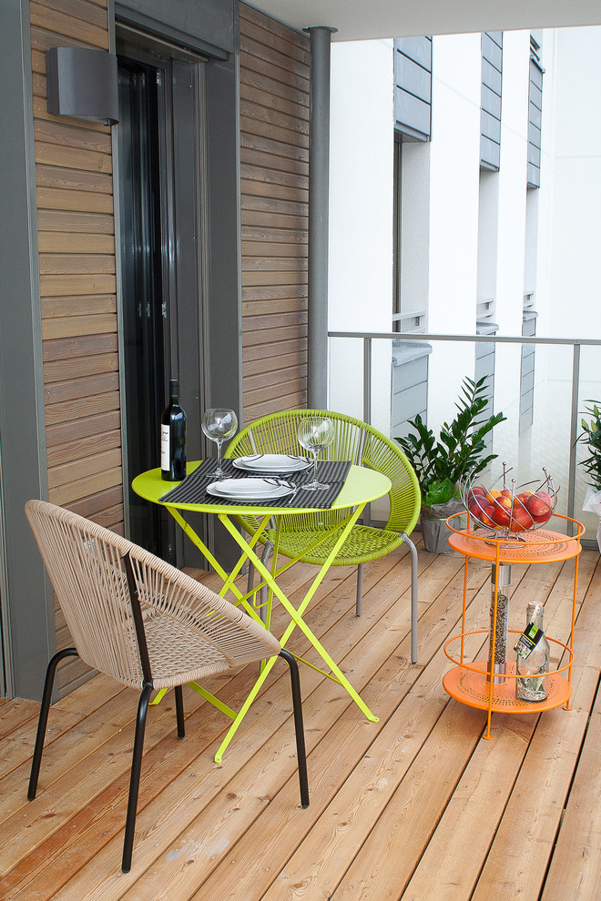 contemporary balcony pop colored furniture in yellow orange and brown wood decking floors dark toned wood siding exterior walls