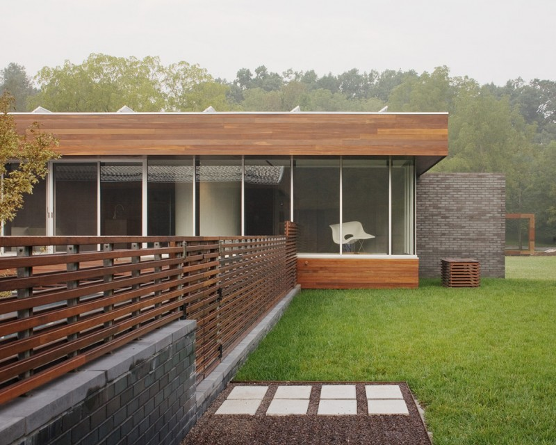 contemporary exterior with dominant glass walls and sliding doors dark toned wood fences with header