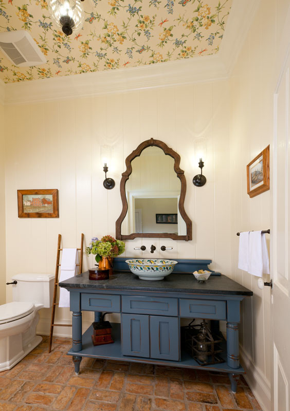country style bathroom vanity dark blue cabinets black marble countertop handpainted bowl sink wood framed mirror white painted vertical wood siding walls terracotta tiles floors wallpaper ceilings