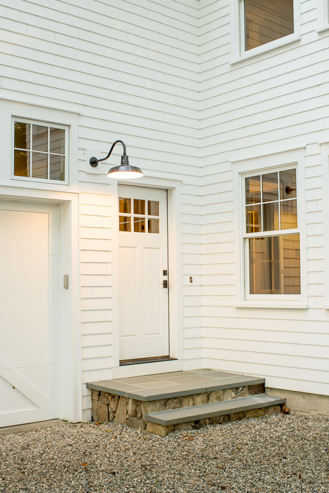 country style exterior idea white front door with narrow glass windows wall mounted spotlight fixture stone floors white siding exterior walls