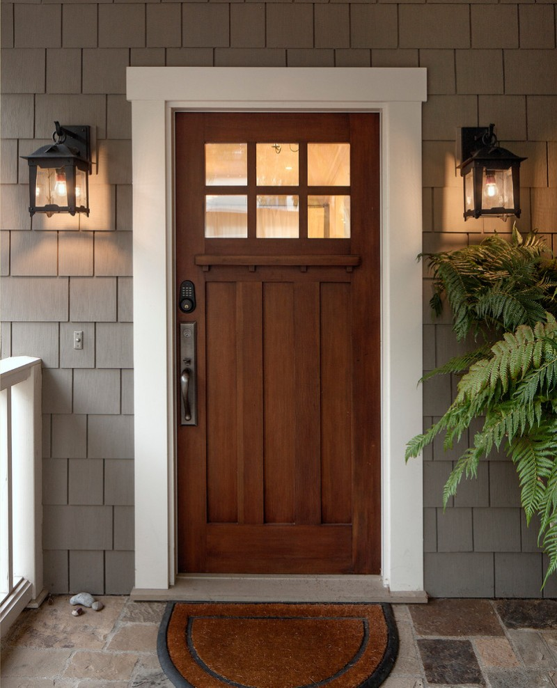 craftsman front door in wood color Loma sconces white painted door trims wood shingles in grey half way round entry rug