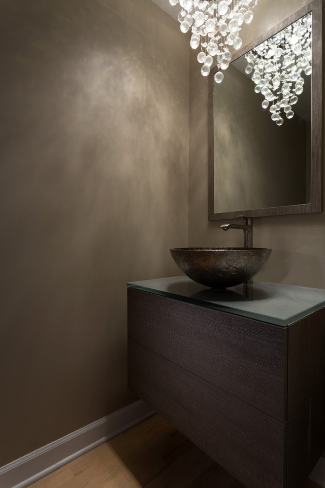 dark & gloomy feel powder room idea deep espresso cabinets with smokey grey countertop dark brass vessel bowl sink stainless steel faucet wood framed mirror gorgeous glass bubbles lighting fixture