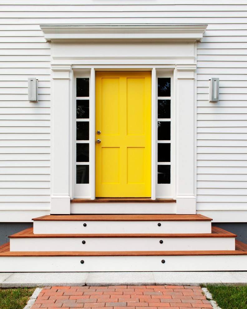 egg yolk colored colonial front door with dark glass sidelights wood exterior floors white siding exterior walls