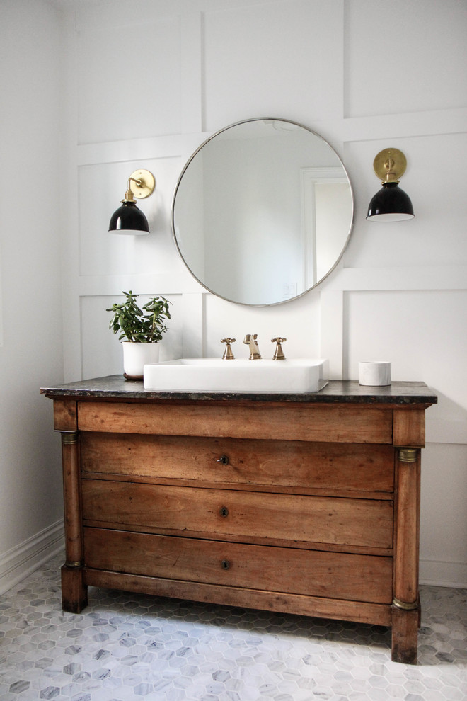 farmhouse bathroom vanity oak cabinets with wood bottoms white farmhouse sink solid black countertop round shaped mirror a pair of vanity lamps