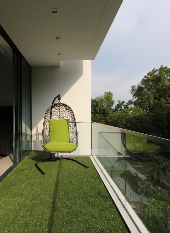 green themed modern balcony idea synthetic green grass carpet glass panel railings white concrete walls sliding glass door