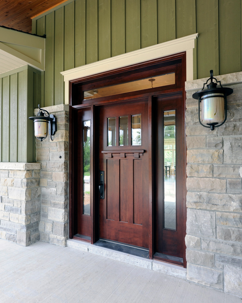 hardwood colonial front door with reflective side windows and transom cultured stone exterior walls for lower part green wood siding upper exterior walls
