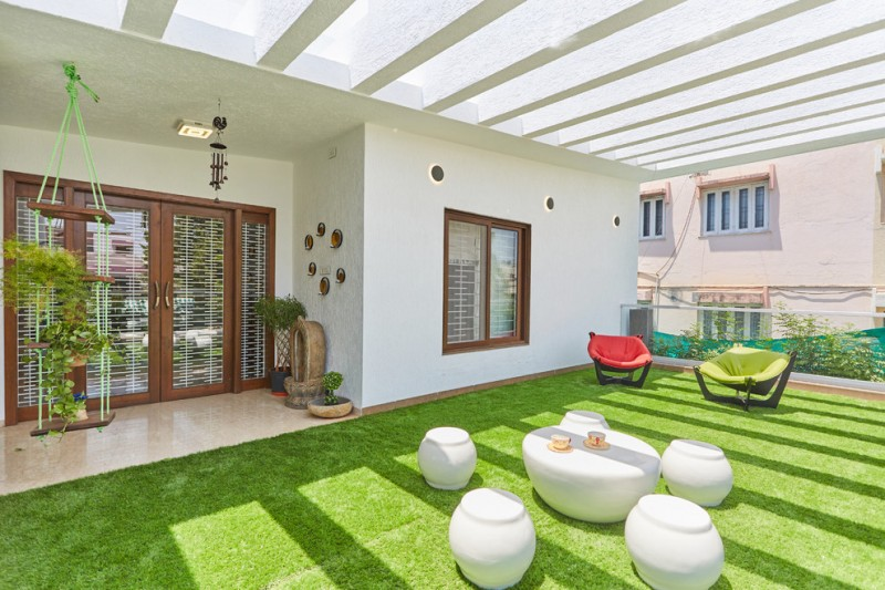 large traditional balcony a cluster of white chairs and table a couple of colorful chairs green grass floors exposed concrete beams ceilings