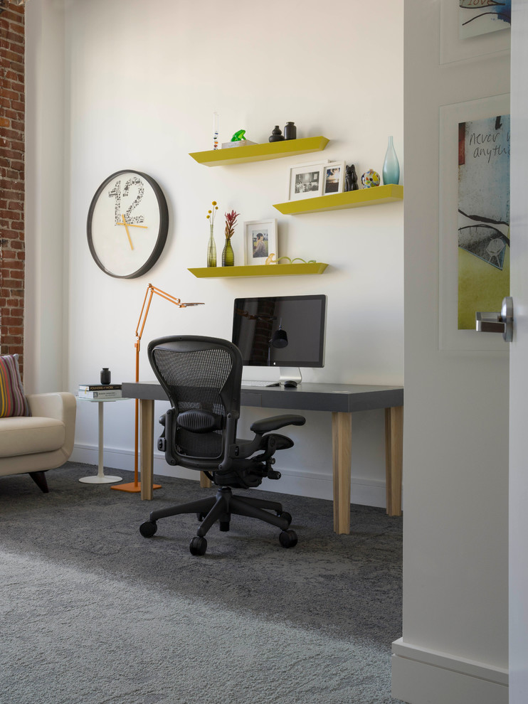 loft home office custom working desk with grey top custom wall shelves in green round shaped wall clock grey carpet