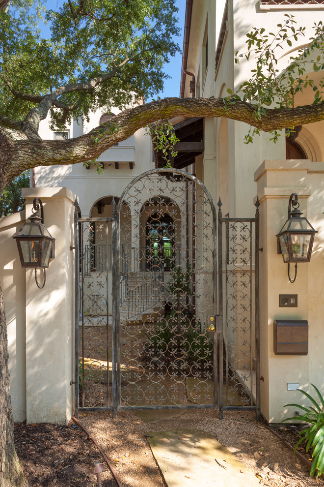 mediterranean landscaping idea with solid concrete walls supported by old & antique iron door gate