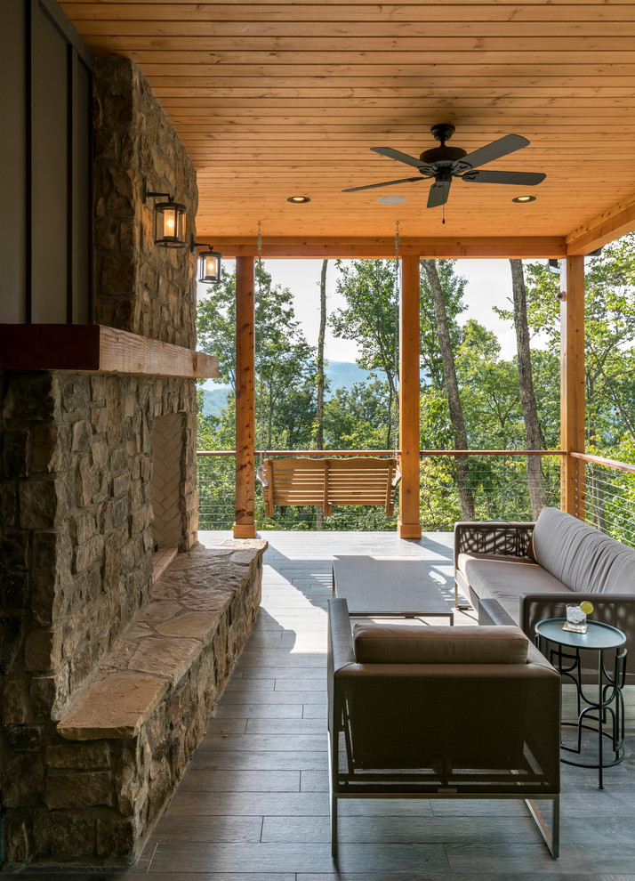 modern craftsman balcony in large size wood decking and railing supported by log pillars outdoor fireplace with stone surroundings dark finishing furniture set wood board ceilings ceiling fan