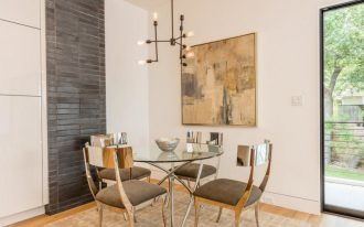 modern dining room modern dining chairs glass round top dining table industrial restoration chandelier contemporary wall art soft cream rug light toned wood floors