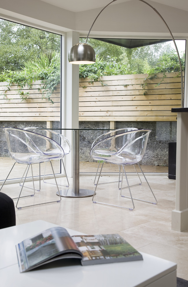 modern outdoor dining space clear acrylic dining chairs round glass top dining table modern floor lamp cedar concrete fencing idea
