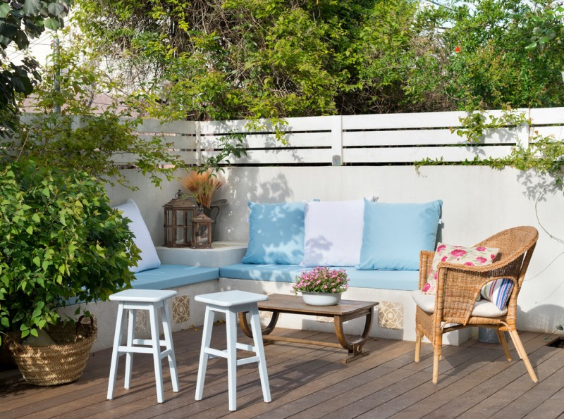 modern patio wood decking floors L shaped concrete seats with accent pillows small side tables in white rattan side chair white landscaping wall