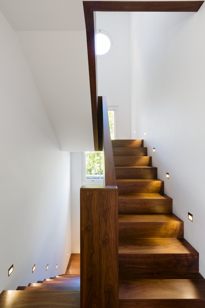 modern style staircase with recessed light fixture on walls