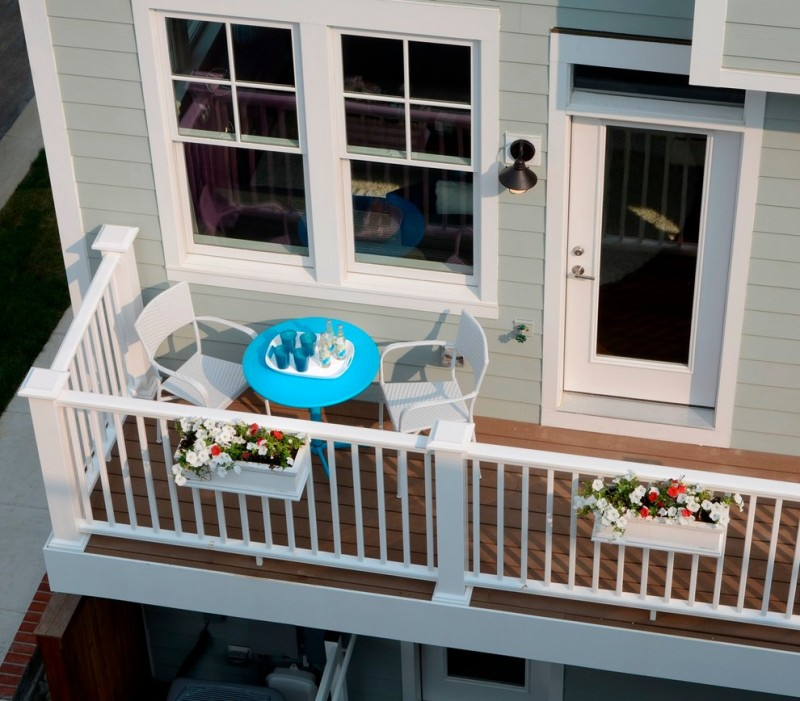 narrow craftsman balcony in dominant white white painting wood rails wood decking white outdoor chairs for two round top turquoise center table grey siding exterior walls white window trims