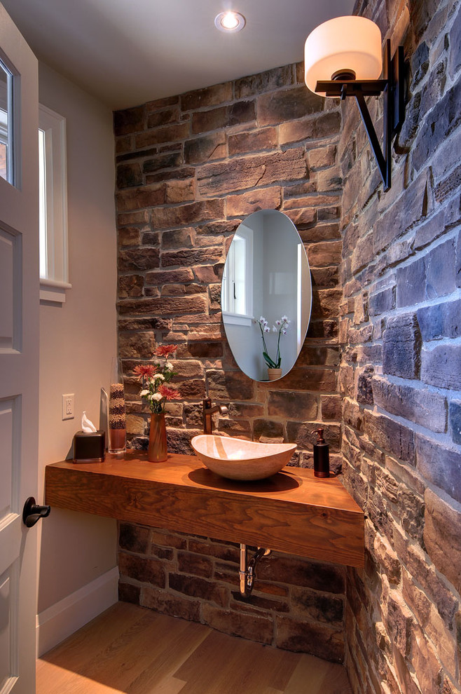 raw rustic powder room with modern touch hardwood vanity counter vessel sink hard textured stones walls medium toned wood floors oval shaped mirror without finishing