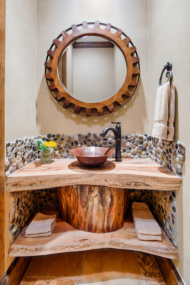 rustic bathroom vanity idea log vanity's counter cooper sink black wrought iron faucet hardwood framed mirror in round shape cream toned walls with stones accents