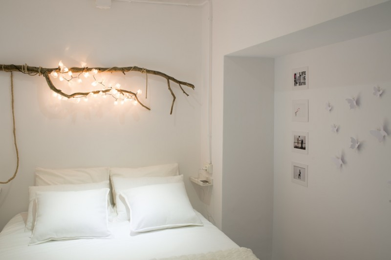 scandinavian style bedroom idea white bedding treatment tree branch light fixture idea