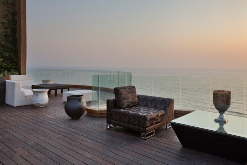 sea facing modern balcony idea with wood decking & glass railing system modern furniture sets several decorative vases
