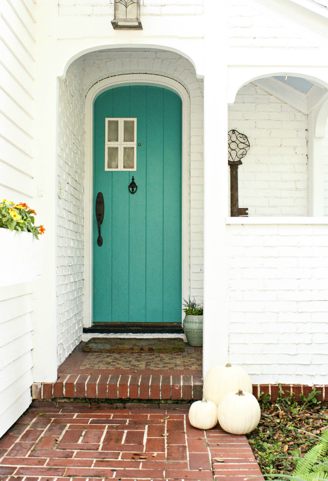 shabby chic colonial front door with blue spa finishing and small window accent pure white brick exterior walls terracotta floors