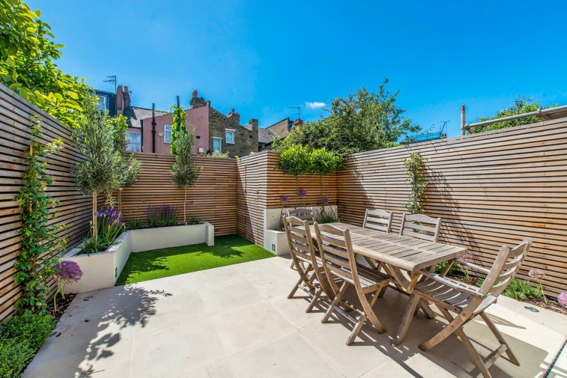 shed fence idea made of cedar slats concrete decking idea white painted concrete plant beds