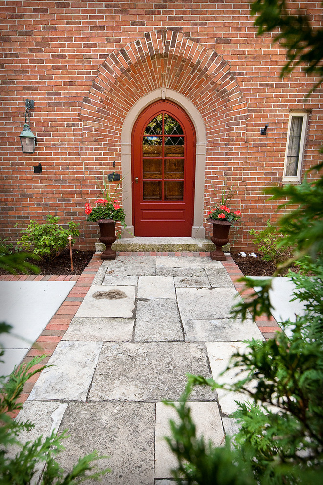 traditional colonial front door in red with curved top and glass panels red brick exterior walls