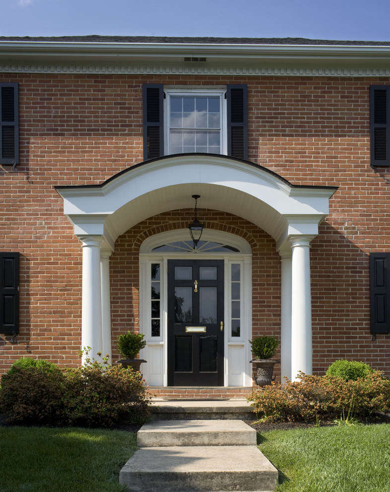 traditional entryway with traditional black front door accented by sidelights and curved top huge white entry gate red bricks exterior walls