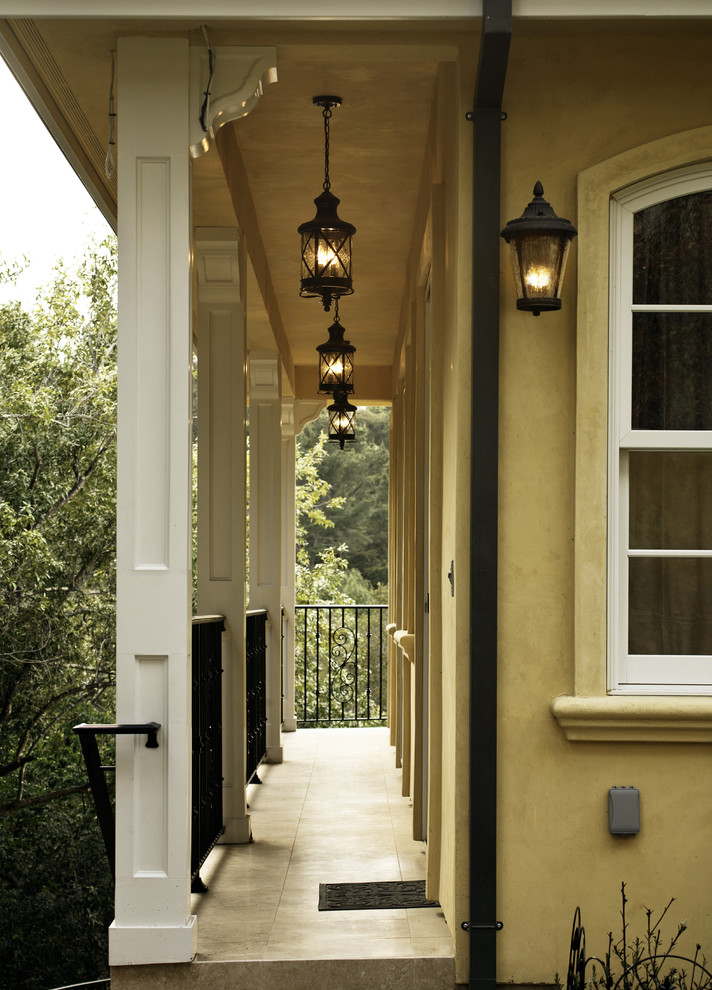 traditional porch idea mustard yellow exterior walls black finished railing system classic style pendant light and sconce