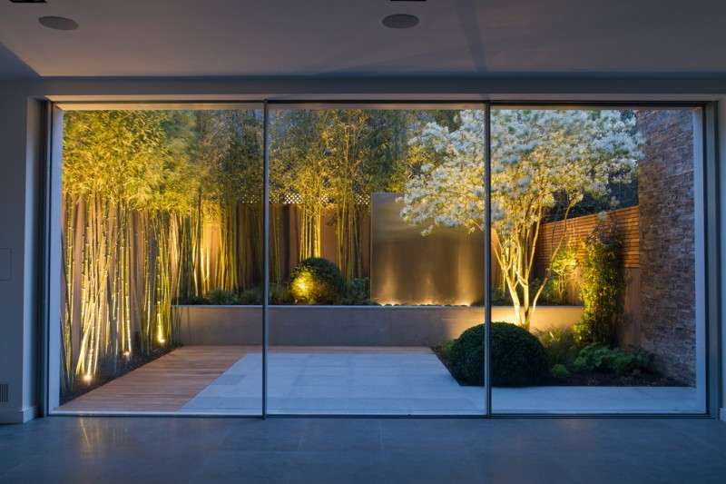 Asian style landscaping idea with lighted trees