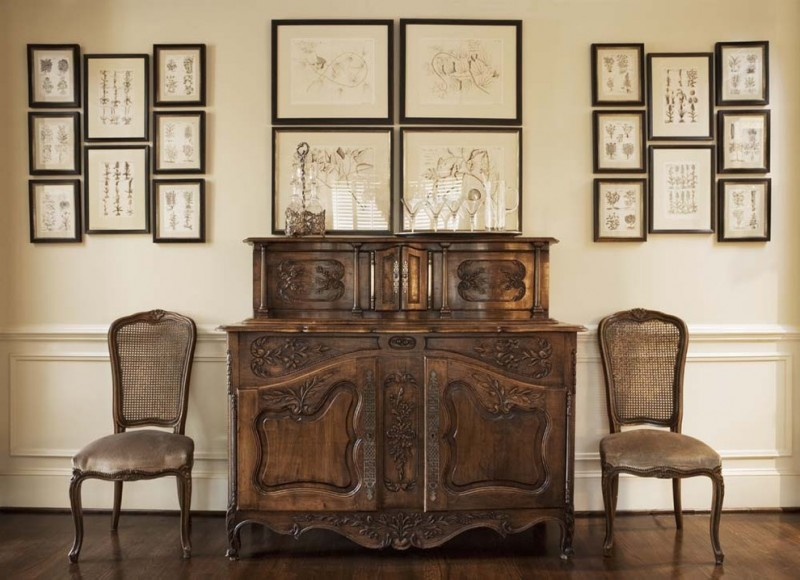 antique look living room ornate dark wood chairs dark toned wood console table with hand crafted details on surfaces dark wood framed wall decors dark wood floors beige walls