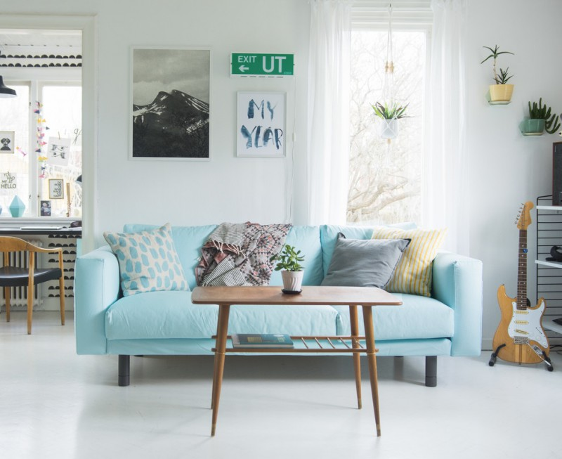 baby blue couch with throw pillows skinny & high legs coffee table made of wood white concrete floors white walls
