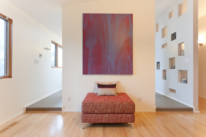 backless couch in red smaller throw pillows abstract painting cream painting walls medium toned wood floors
