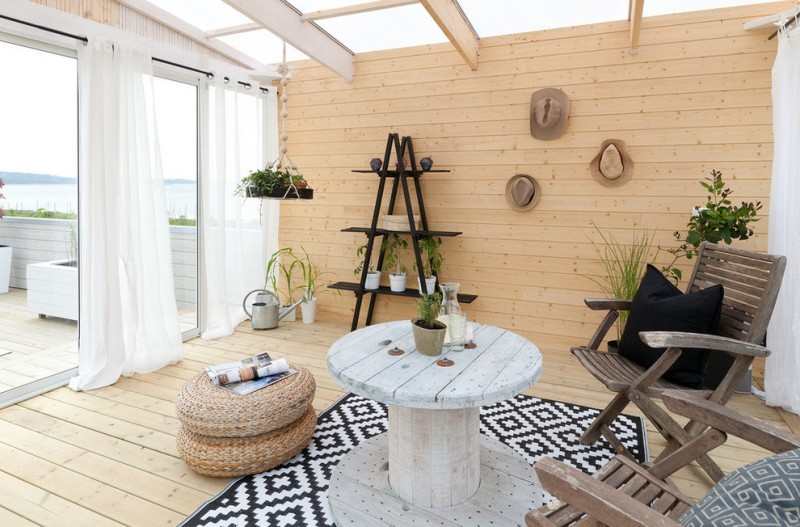 beach style sunroom with soft toned interior medium toned wood siding walls and floors whitewashed round top wood table black white modern area rug wood woven side chair stand rack in black
