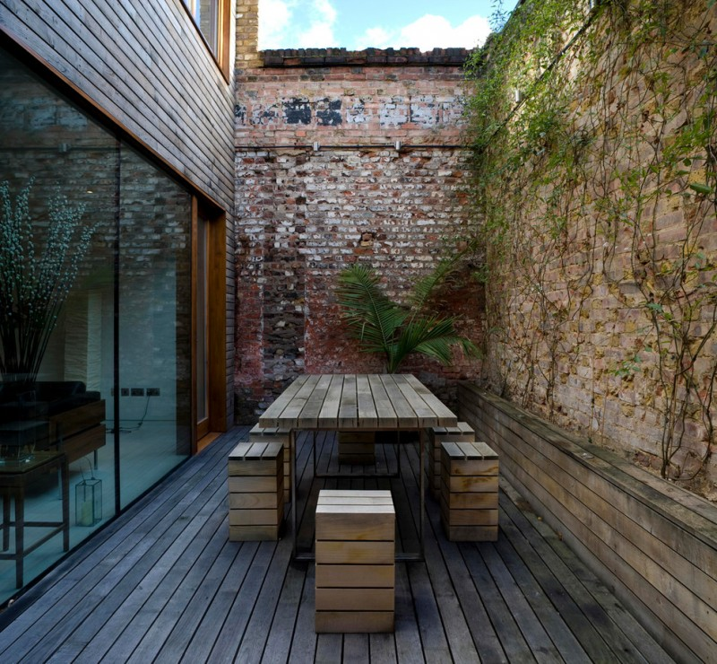 chic contemporary patio cube shaped wood chairs wood board table shabby red bricks walls with vines wood board floors