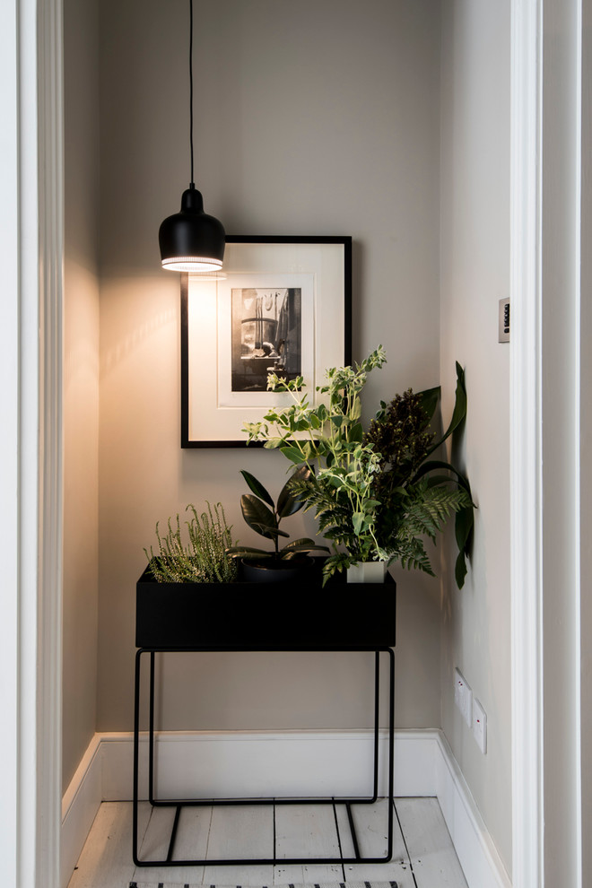 contemporary entryway black finishing planter with thin legs pendant with black shade black framed photograph
