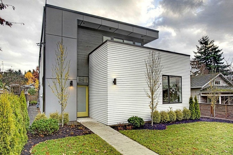 contemporary exterior idea white siding exterior walls yellow front door black cylinder wall sconces concrete pathway