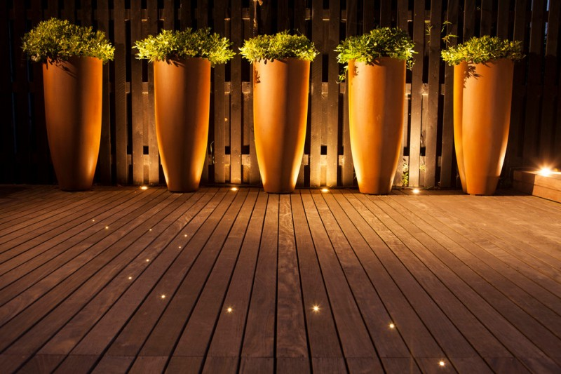 contemporary patio idea wood board floors with recessed small lighting fixtures several clay burnt planters with greens wood fences