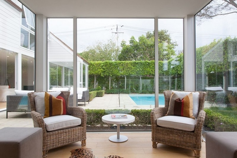 contemporary sunroom design rattan chairs round top coffee table in white medium toned wood floors glass panels