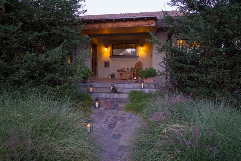 craftsman exterior idea low lighted wall sconces Windsor lanterns paving pathway wooden chair