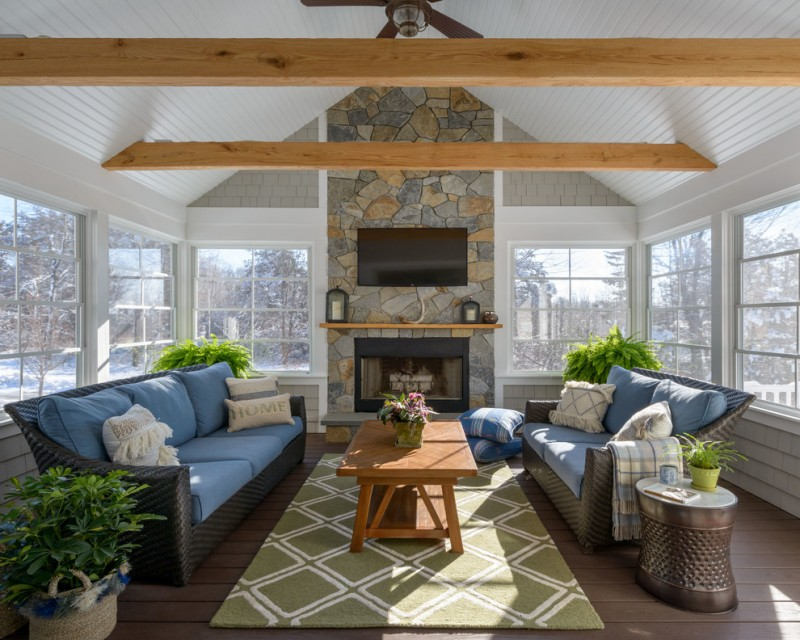 craftsman sunroom dark woven sofas with blue seaters medium toned coffee table green area rug with white modern motifs dark toned wood floors metal side table with round top