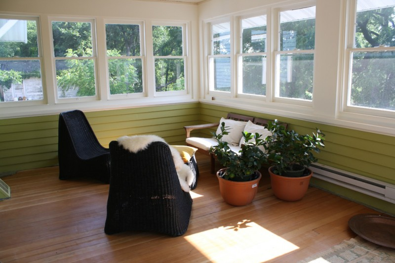 craftsman sunroom medium sized windows black chairs wood chair medium sized planters medium toned wood floors green siding walls