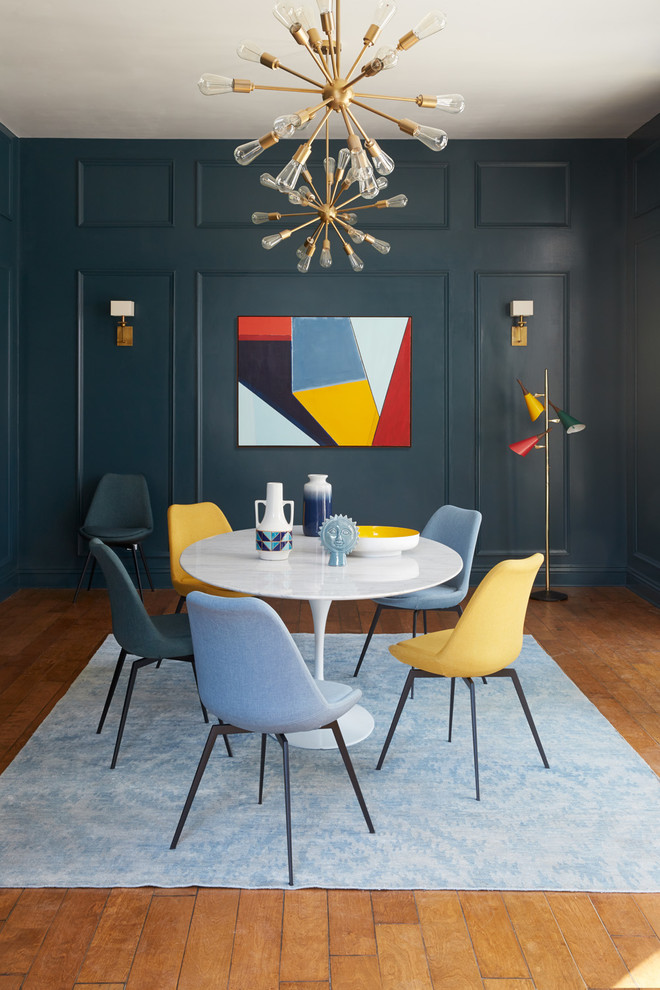 dark blue wood panel wall decorative pendant multicolored abstract painting colorful midcentury modern dining chairs white round top dining table light blue rug medium toned wood floors